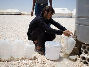 A Syrian refugee in Jordan's Zaatari camp retrieves water. Jordan is one of the most water-scarce countries on earth (File Archive/AFP)