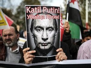 "A protester holds a poster depicting Russian President Vladimir Putin and reading ""Putin, killer!"" during a demonstration in Istanbul, on November 27, 2015. (AFP/ Cagdas Erdogan)"