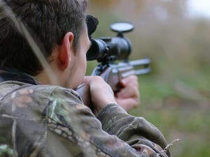 A man in camouflage and with guns in a forest belt on a spring hunt. (Shutterstock/ File Photo)