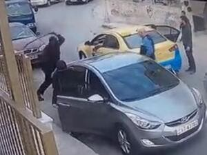 The man is seen taking a sword out of his trunk and striking the taxi driver's arm with it before being pushed away by bystanders and a woman who was with him in the vehicle (Facebook)