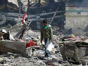 A Yemeni boy walks amid the ruins of a school and a bowling club hit by an air-strike carried out by the Saudi-led coalition, in the capital Sanaa, on February 12, 2016. (AFP/Mohammed Huwais)
