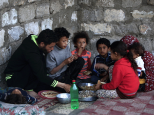 A Palestinian family share an Iftar meal as they break their fast during the Muslim holy fasting month of Ramadan on May 13, 2019 in the southern Gaza Strip refugee camp of Khan Yunis.