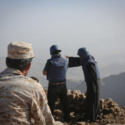 A Yemeni soldier looks at two journalists reporting the event