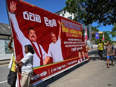 Supporters of Sri Lanka Podujana Peramuna (SLPP) party presidential candidate Gotabaya Rajapaksa carry cut-out placards to celebrate in Colombo on November 17, 2019. (AFP)