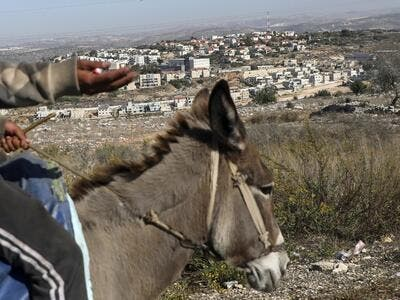A man rides on a donkey in the Palestinian village of Kifl Hares opposite the Israeli Jewish settlement of Revava (background) on November 19, 2019. Israeli Prime Minister Benjamin Netanyahu hailed a US announcement that it no longer considers settlements in the West Bank and annexed east Jerusalem illegal, but the Palestinians pledged new measures to oppose it. Jaafar ASHTIYEH / AFP