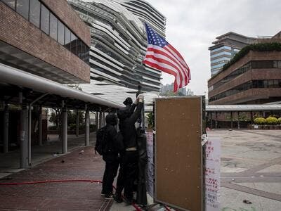 Protesters raise a US flag inside the Hong Kong Polytechnic University in the Hung Hom district of Hong Kong on November 20, 2019. A dwindling number of exhausted pro-democracy protesters barricaded inside the Hong Kong university defied warnings on November 19 to surrender, as a police siege of the campus stretched through a third day and China sent fresh signals that its patience with nearly six months of unrest was running out.