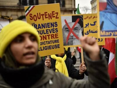 "Protesters hold placards reading ""Support Iranians risen up against the religious dictatorship"" during a demonstration in support of the Iranian people amid a wave of protests spreading throughout Iran, on January 6, 2018, in Paris. Photo AFP"