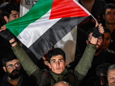 A man holds a flag of Palestine as protesters take part in a demonstration in front of the US consulate in Istanbul on 29 January, 2020 (AFP)