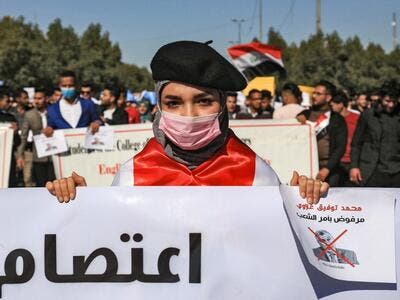 "In this file photo taken on February 2, 2020, An Iraqi student wearing a beret and a surgical mask holds signs with a red X mark on the face of the new Iraqi prime minister designate Mohammad Allawi reading in Arabic ""rejected by order of the people"" during a demonstration against him in the central holy shrine city of Karbala. (AFP)"