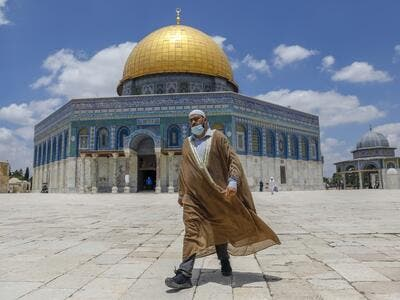 A Palestinian man walks outside the Dome of the Rock Mosque in Jerusalem's al-Aqsa compound amid the COVID-19 pandemic, on July 9, 2020. AHMAD GHARABLI / AFP