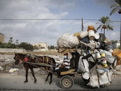 A Palestinian man collects plastic containers on his horse cart while wearing a protective mask due to the COVID-19 coronavirus in Deir al-Balah in the central of Gaza Strip on October 1, 2020. MOHAMMED ABED / AFP