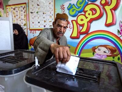 A man casts his ballot at a polling station in El-Ayyat, south of the Egyptian capital on October 24, 2020, during the first stage of the lower house elections. Polling stations opened in Egypt for parliamentary elections in which there was little doubt of a sweeping victory for supporters of hardline President Abdel Fattah al-Sisi. Some 63 million voters out of Egypt's more than 100 million people are eligible to elect 568 of the 596 lawmakers in the lower house, widely seen as a rubber-stamp body for exec