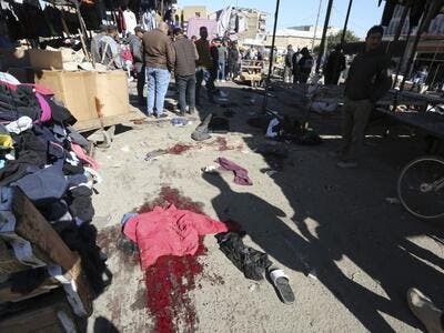 A picture shows the scene of a twin suicide bombing on a bustling commercial street in the heart of Baghdad on January 21, 2021. The toll in a twin suicide bombing in an open-air Baghdad market morning topped 20 dead and 40 wounded, an interior ministry official told AFP. The ministry said the first suicide bomber had rushed into the market and claimed to feel sick, so that people would gather around him. He then detonated his explosives. Sabah ARAR / AFP