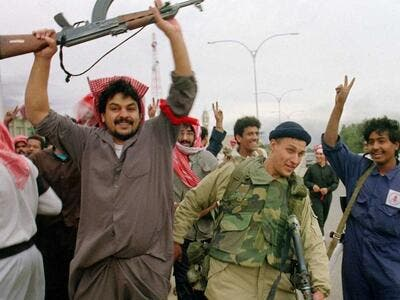 Kuwaiti resistance fighters celebrate with a member of the US Marine Special forces on February 26, 1991, after the Marines entered the small town of Sabahiah, 9 miles from the capital of Kuwait City. (AFP File Photo)