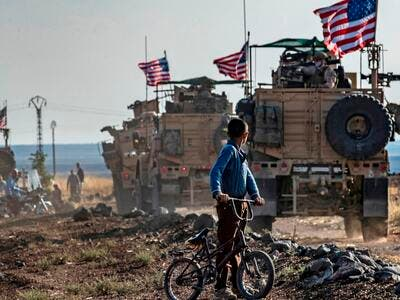A Syrian boy on a bicycle watched a convoy of US armored vehicles drive away on a dirt road in northeastern Syria. Delil Souleiman (AFP via Getty Image File Photo)