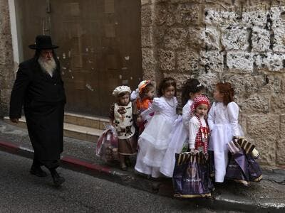 Ultra-Orthodox Jewish children dressed in costumes to celebrate Purim, walk in the street a day ahead of the official holiday, in the Mea Shearim neighbourhood in Jerusalem, on February 24, 2021. The carnival-like Purim holiday is celebrated with parades and costume parties to commemorate biblical story of the deliverance of the Jewish people from a plot to exterminate them in the ancient Persian empire , as recorded in the Book of Esther. MENAHEM KAHANA / AFP