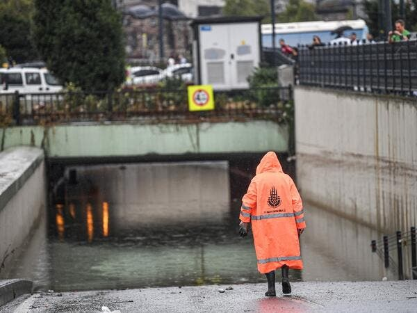 A municipality worker walks near a flooded underpass after a heavy rainfall, in Eminonu district, Istanbul, on August 17, 2019. Turkey's mega city Istanbul was lashed by a heavy rainstorm on August 17, killing a homeless man and leaving parts of the historic Grand Bazaar flooded.  Ozan KOSE / AFP