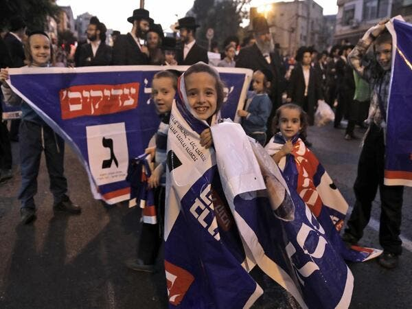 Children play with electoral banners as thousands of Ultra Orthodox Jews attend an election campaign rally of the Yahadut Hathora (United Torah Judaism) at the centre of Jerusalem on September 15 2019, two days ahead of the Israeli general elections. MENAHEM KAHANA / AFP