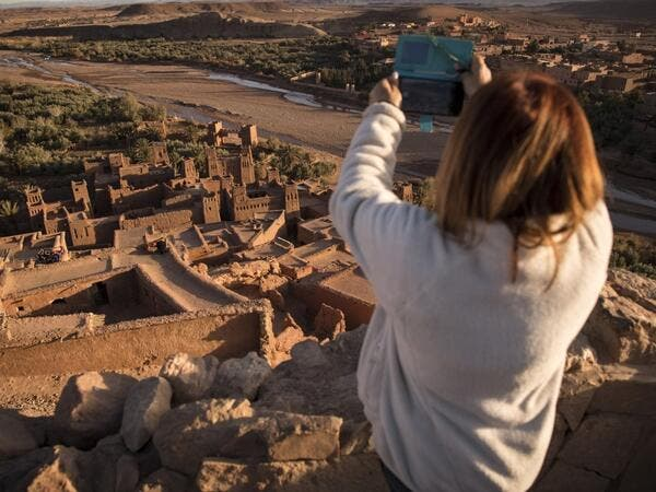 "A tourist uses her phone to photograph the Kasbah (ancient fortress) of Ait-Ben-Haddou, where scenes depicting the fictional city of Yunkai from the hit HBO television series ""Game of Thrones"" were filmed, about 32 kilometres northwest of the city of Ouarzazate south of Morocco's High Atlas mountains on January 27, 2020.  FADEL SENNA / AFP"