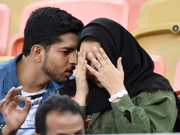 A picture taken on January 12, 2020 shows a Saudi couple attending a football match at King Abdullah Sport City Stadium in Jeddah. In Saudi Arabia's rigid past, religious police once swooped down on rose sellers and anyone peddling red paraphernalia around Valentine's Day, but now a more open -- albeit risky -- dating culture is taking root. Pursuing relationships outside of marriage in the conservative Islamic kingdom once amounted to a death wish, and would-be Romeos resorted to pressing phone numbers up