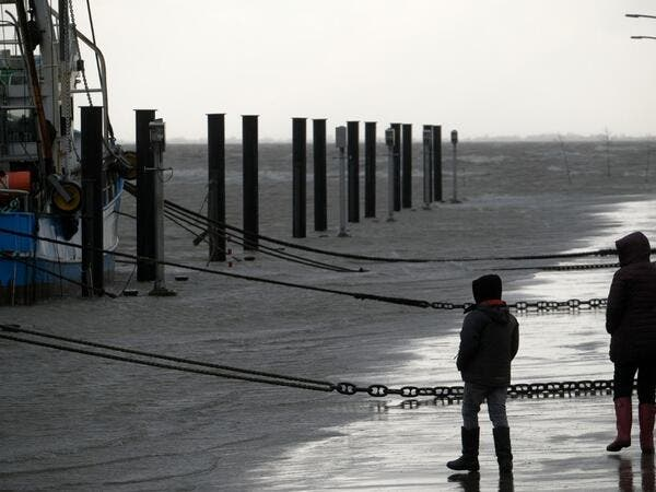 People walk near fish trawlers at the flooded harbor of Wremen, on the North Sea near Bremerhaven, northern Germany, on Febuary 11, 2020. Fierce winds and heavy rains claimed at least six lives across northern Europe on February 11, 2020, as Storm Ciara disrupted travel, grounded hundreds of flights, flooded roads and left vast areas without power. Patrik Stollarz / AFP