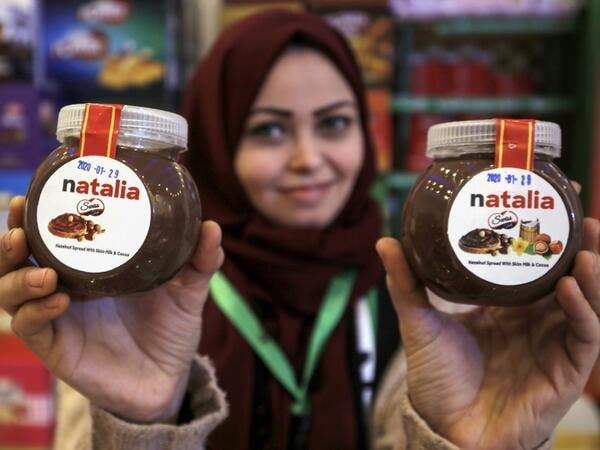 A shop employee holds up jars of a Gazan version of a world famous spread, dubbed 'Natalia', in Gaza city on February 12, 2020. Al-Arees's products are Gazan but their components are not, as few of the basic raw ingredients are produced in the impoverished Mediterranean coastal strip. MOHAMMED ABED / AFP