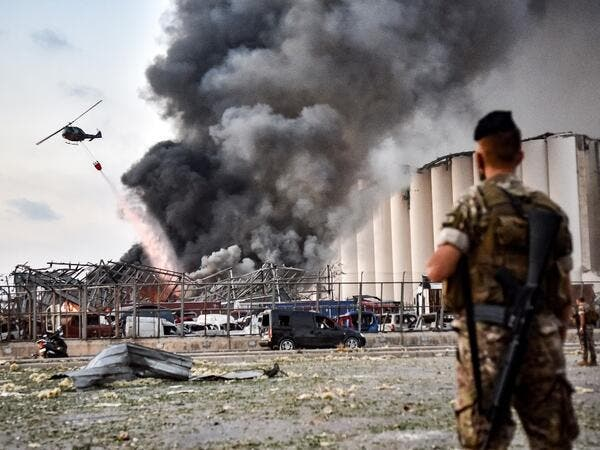 Lebanese army soldiers stand while behind a helicopter puts out a fire at the scene of an explosion at the port of Lebanon's capital Beirut on August 4, 2020. STR / AFP