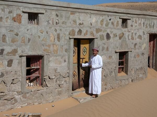 Mohammed al-Ghanbousi, a former inhabitant of Wadi al-Murr, stands next to his abandoned house in the Omani village, about 400 kms (250 miles) southwest of the capital Muscat, on December 31, 2020. Encroaching desert sands have left little evidence that Wadi al-Murr ever existed, but former inhabitants, while resigned to its destruction, are trying to preserve its memory. MOHAMMED MAHJOUB / AFP