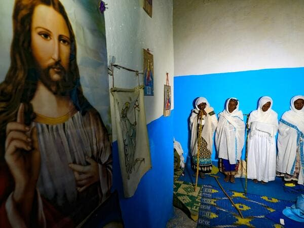 Ethiopian refugees who fled the Tigray conflict attend the Coptic Christmas midnight mass with local believers, inside an Ethiopian Orthodox church built by former Ethiopian refugees, at a village next to Um Raquba refugee camp in Gedaref, eastern Sudan,late on January 6, 2021. ASHRAF SHAZLY / AFP