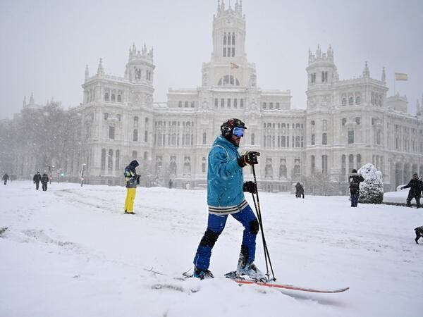 A man skis in Cibeles square amid a heavy snowfall in Madrid on January 9, 2021. Heavy snow fell across much of Spain, leaving huge areas blanketed in white as Storm Filomena brought wintry weather not seen in decades to the Iberian peninsula. GABRIEL BOUYS / AFP
