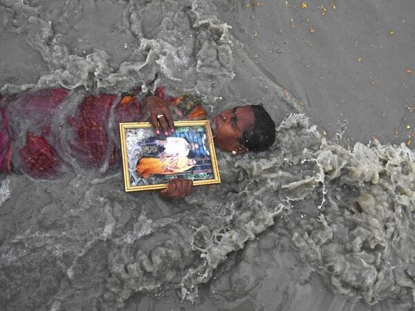 A Hindu pilgrim holds a picture of herself with late husband as she takes a holy dip at the confluence of Ganges and the Bay of Bengal during the Gangasagar Mela on the occasion of Makar Sankranti, a day considered to be of great religious significance in Hindu mythology, at Sagar Island, around 150 kms south of Kolkata on January 14, 2021. Dibyangshu SARKAR / AFP