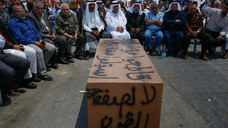 "Palestinian men sit around a makeshift coffin with the words ""No to the deal of the century"", during a protest against a US-led meeting this week in Bahrain on the Palestinian-Israeli conflict, in the village of Yatta near the West Bank city of Hebron, on June 24, 2019. (AFP/ File Photo)"