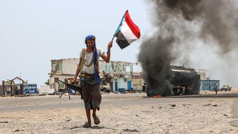 A fighter of the UAE-trained Security Belt Force, dominated by members of the Southern Transitional Council (STC) which seeks independence for south Yemen, walks with a separatist flag past an oil tanker set ablaze in Aden. (AFP/ File Photo)