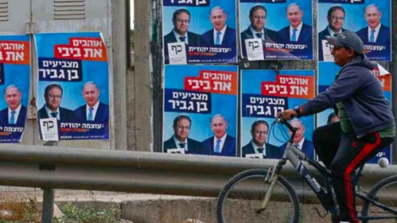 A Palestinian rides his bicycle past electoral campaign posters depicting Israeli Prime Minister Benjamin Netanyahu (right) and far-right politician Itamar Ben Gvir in the West Bank. HAZEM BADER/AFP