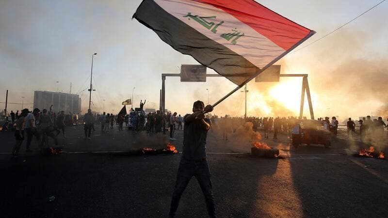 An Iraqi protester waves the national flag during a demonstration against state corruption, failing public services, and unemployment, in the Iraqi capital Baghdad on October 5, 2019. (AFP/ File Photo)