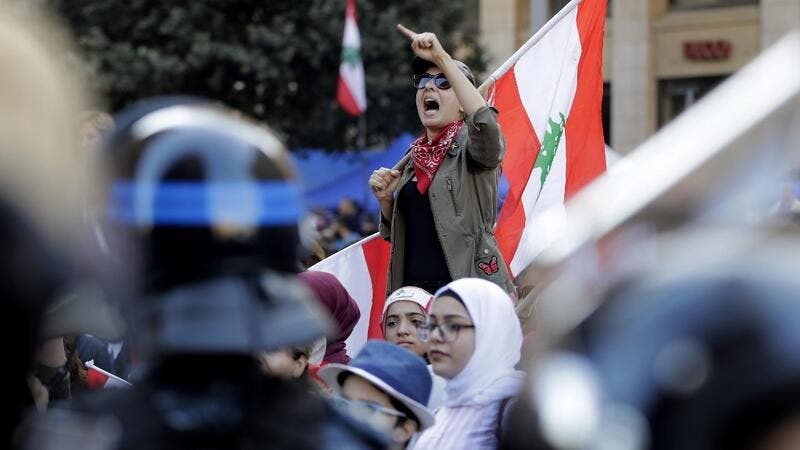 A Lebanese protester holds a national flag as she chants slogans during a demonstration at Riad al-Solh square near the government palace and the parliament headquarters in the capital Beirut's downtown district on November 19, 2019. (AFP/ File Photo)