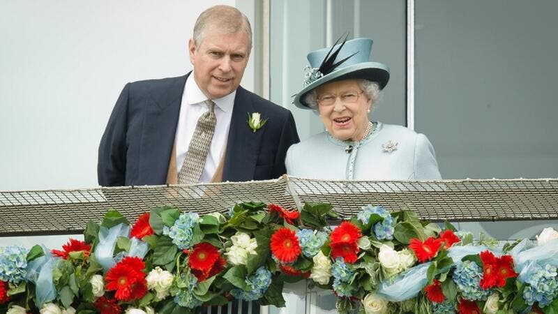 Prince Andrew, the Duke of York (L) speaks to Queen Elizabeth II on the Queens stand during Derby day at the Epsom Derby Festival, in Surrey, southern England, on June 1, 2013. (AFP/ File Photo)