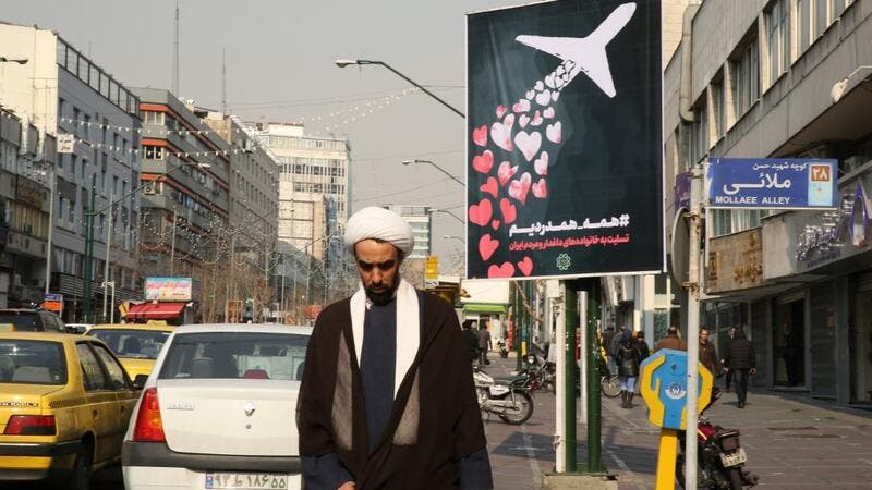 An Iranian cleric walks past a poster honouring the victims of a Ukrainian passenger jet accidentally shot down in the capital last week, in front of the Amirkabir University in the capital Tehran, on January 13, 2020.  (AFP/ File Photo)