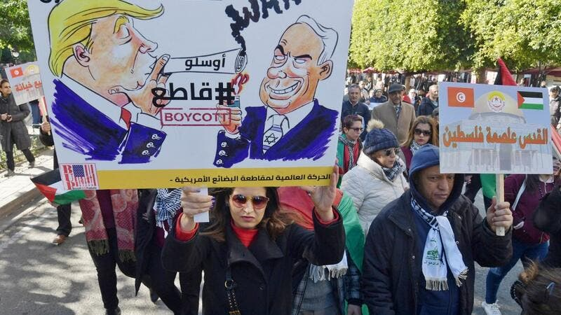"Tunisian demonstrators hold up placards against US President Donald Trump's Middle East peace plan proposal during a protest on February 5, 2020 in Tunis. Arabic writing on placards reads: ""Jerusalem is the capital of Palestine"" (R) and ""Down with the 'Deal of the Century', #Boycott"" next to cartoon images of Trump and Israel's Prime Minister Benjamin Netanyahu. FETHI BELAID / AFP"