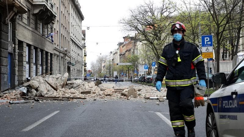 A Croatian fireman walks past rubbles laying on the ground, in a street of downtown Zagreb, on March 22, 2020, after an earthquake hit the country at 06:00 am (0500 GMT). A 5.3-magnitude earthquake shook the Croatian capital of Zagreb on March 22, 2020, damaging buildings and cutting electricity in a number of neighbourhoods. Damir SENCAR / AFP
