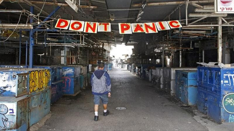"A man passes under a ""Don't Panic"" banner hanging at the entrance of Shuk HaCarmel (Caramel) market in the Israeli coastal city of Tel Aviv on March 24, 2020 after Israel barred residents from leaving home for non-essential reasons and stopped night-time public transport, tightening already strict measures to fight the spread of coronavirus. JACK GUEZ / AFP"