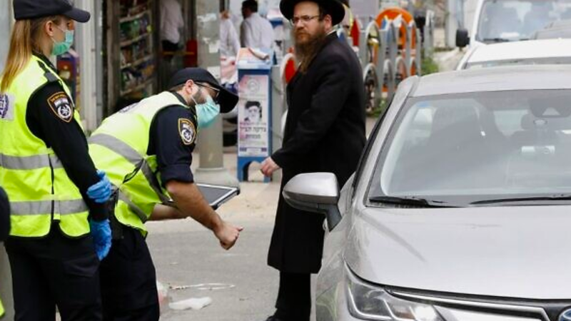 Israeli police talk to a driver at a checkpoint in Bnei Brak, a predominantly ultra-Orthodox city east of Tel Aviv, on March 31, 2020, as part of measures to curb the spread of the coronavirus. (Jack Guez/AFP)