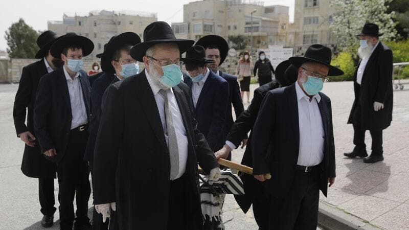Pallbearers from the Ultra-Orthodox Jewish burial society (Hevrat kadishah), wearing surgical masks as a precaution against COVID-19 coronavirus disease, carry the coffin of an elderly man (not a COVID-19 victim) during a funeral outside the Shamgar funeral house in Jerusalem on April 5, 2020. MENAHEM KAHANA / AFP