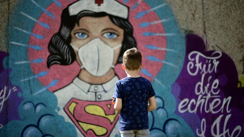 A boy stands in front of a graffiti painted by artist Kai 'Uzey' Wohlgemuth featuring a nurse as Superwoman on a wall in Hamm, western Germany, on April 8, 2020 refering to the spread of the novel coronavirus COVID-19. Ina FASSBENDER / AFP