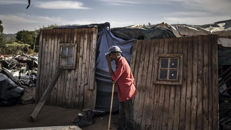 A resident of Plot 323 in Wilgespruit, Johannesburg, pauses on May 08, 2020 in front of a wooden shack during a ministerial visit aimed to ensure that the vulnerable residents of the informal settlement are soon properly accommodated in temporary residential units. MARCO LONGARI / AFP