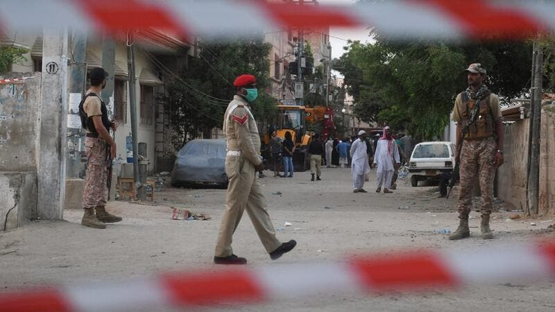 Security personnel patrol on a cordon off a street a day after a Pakistan International Airlines aircraft crashed in a residential area in Karachi on May 23, 2020. Ninety-seven people were killed and two survived when a passenger plane crashed into homes in Pakistan's southern city of Karachi, health officials said on May 23. Asif HASSAN / AFP