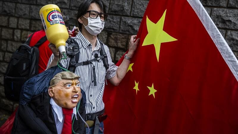 A pro-China activist holds an effigy of US President Donald Trump during a protest outside the US consulate in Hong Kong on May 30, 2020, in response to US President Donald Trump saying on May 29 he would strip several of Hong Kong's special privileges with the United States and bar some Chinese students from US universities in anger over Beijing's bid to exert control in the financial hub. ISAAC LAWRENCE / AFP