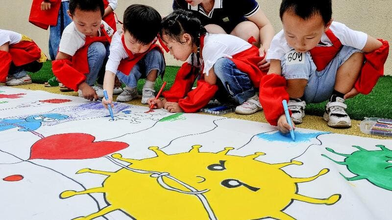 Childern draw an image showing people's efforts against the COVID-19 coronavirus at a kindergarten during the Childern's Day in Shangrao in China's central Jiangxi province on June 1, 2020. STR / AFP