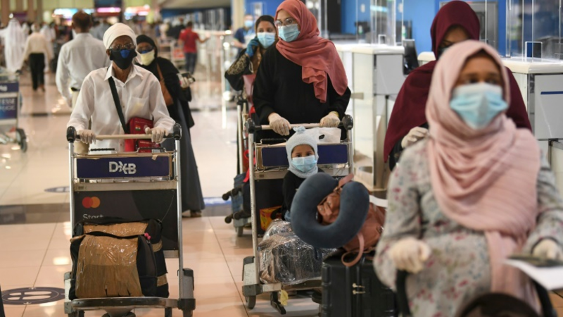 Indian nationals gather at the Dubai International Airport before leaving the country on a flight back to their country, May 7, 2020. /AFP