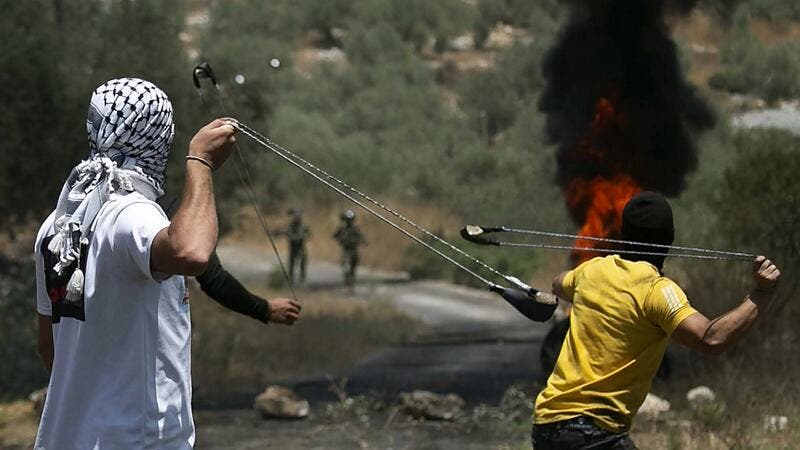 Palestinian protesters use slingshots to hurl stones towards Israeli forces during a demonstration in the village of Kfar Qaddum in the occupied West Bank against the Jewish state's plans to annex part of the Palestinian territory on July 3, 2020. Rival Palestinian factions Fatah and Hamas pledged the previous day a united campaign against Israel's prospective plans to annex territory in the occupied West Bank, in a rare joint press conference, spurred by their common opposition to US President Donald Trump